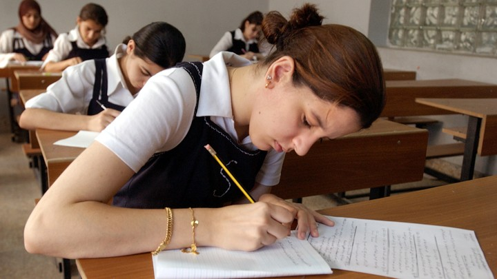 Students in uniform take an exam in a classroom using pencil and paper.