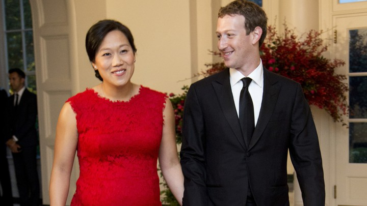 Mark Zuckerberg and Priscilla Chan walk while holding hands and wearing formalwear.