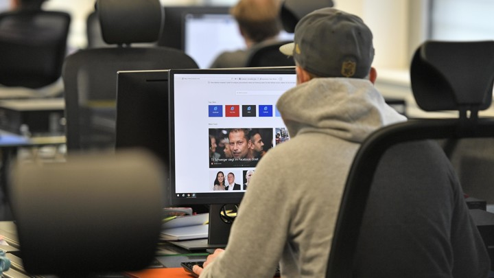 A man looking at Facebook content on a computer screen