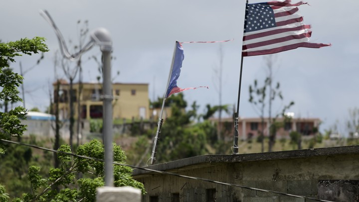 The U.S. flag, next to a damaged Puerto Rican flag, flies in the municipality of Yabucoa.