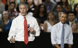 Duncan speaking into a microphone with Obama behind him