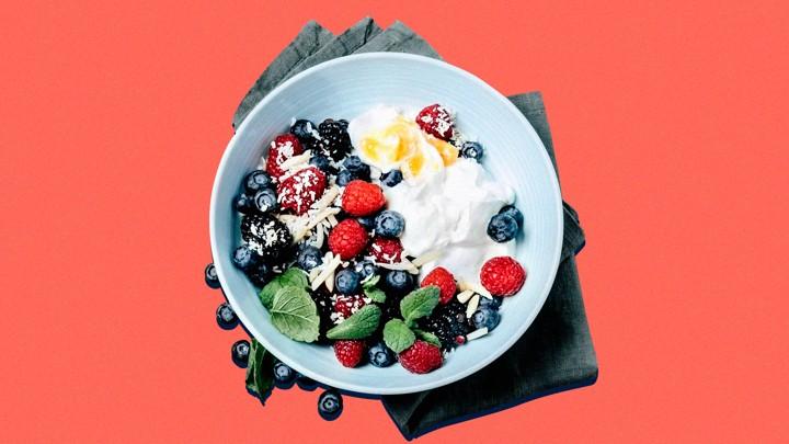 A white bowl with yogurt, blueberries, raspberries