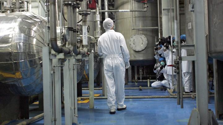 A technician in scrubs walking among machinery