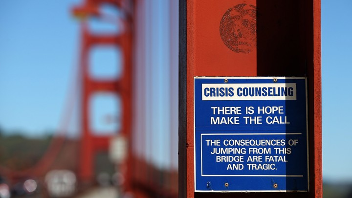 """A blue and white sign attached to the Golden Gate Bridge that reads """"There is hope, make the call"""""""