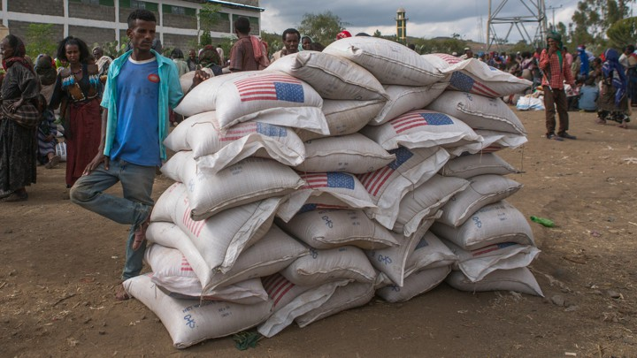 A man standing on a dirt road next to several large bags of food with the American flag on them