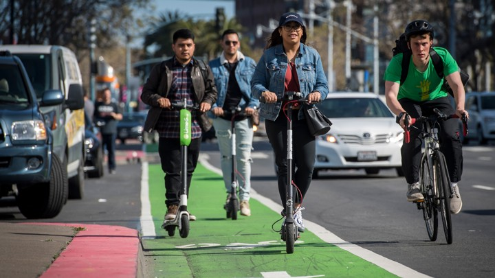 A group of people rides electric scooters from Lime and Bird in a bike lane while a cyclist passes them.