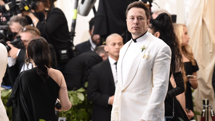 Elon Musk wearing a white suit