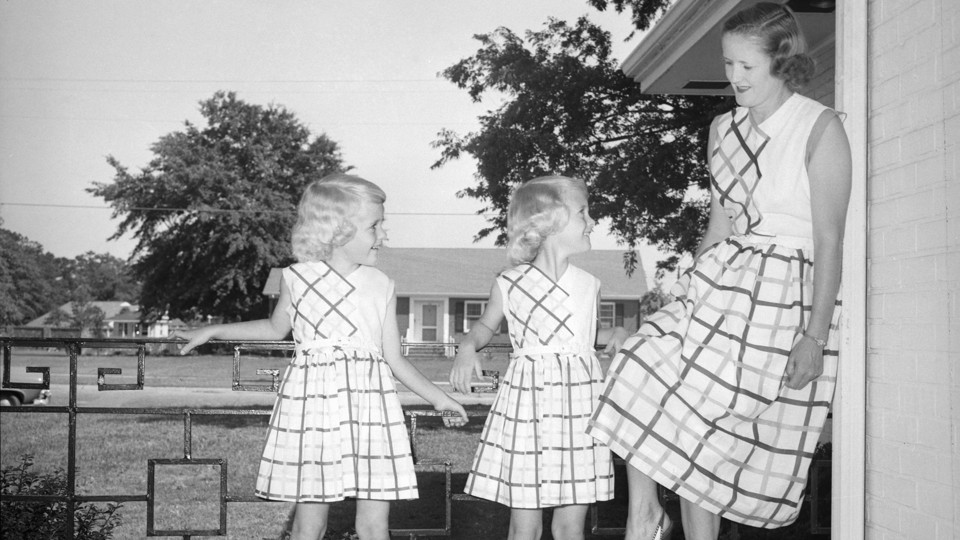 A mom and her daughters pose in the front of their Southern California home in the early 1950s