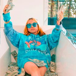A young girl wearing a blue hoodie and blue sunglasses sitting in a bathtub full of dollar bills