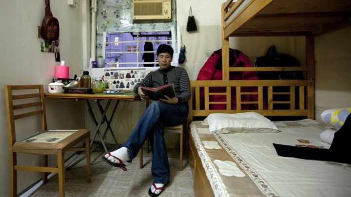 Li Kuanxin, A 48 Year Old Man, Poses For Photos In His 100 Square Feet  Subdivided Flat Inside An Industrial Building In Hong Kong January 19, 2012.