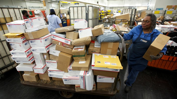 A U.S. Postal Service employee stands next to a cart full of packages.