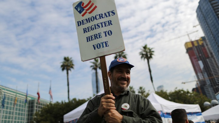 "A Democratic Party worker holds up a ""register to vote"" sign."
