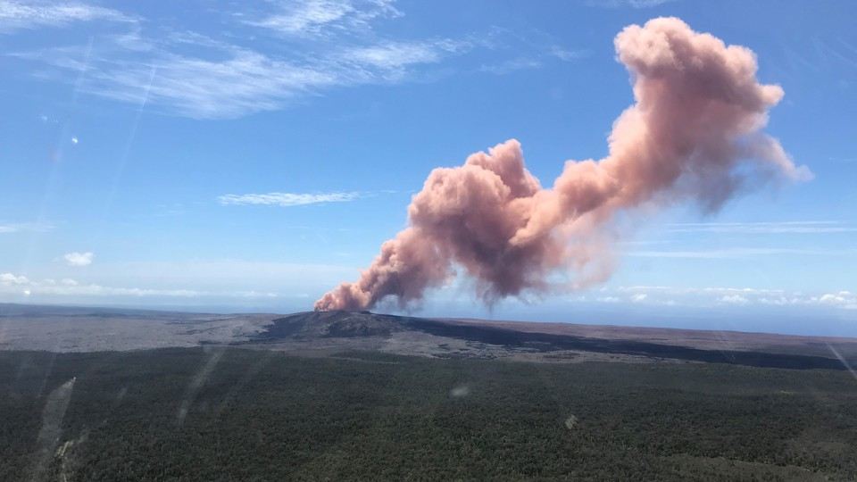 A plume of red-gray ash rises out of a Hawaiian volcano.