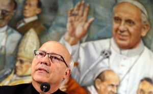 Pérez speaking in front of a mural of Pope Francis
