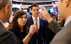 Stacey Cunningham in conversation with three men at the New York Stock Exchange