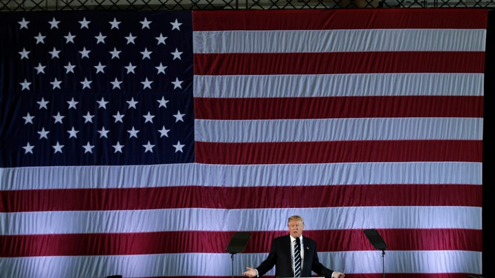 President Trump speaking in front of a large American flag