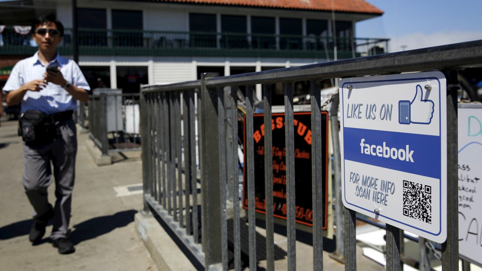 "A man walks by a ""Like Us on Facebook"" sign"