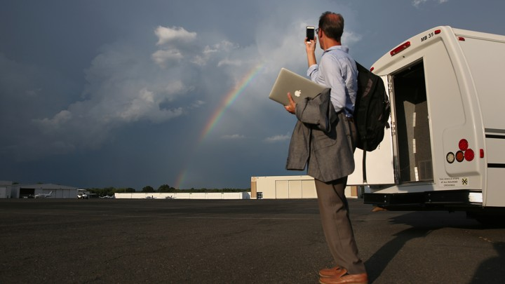A man in business clothes carrying a laptop and a backpack uses a smartphone to take a picture of a rainbow.