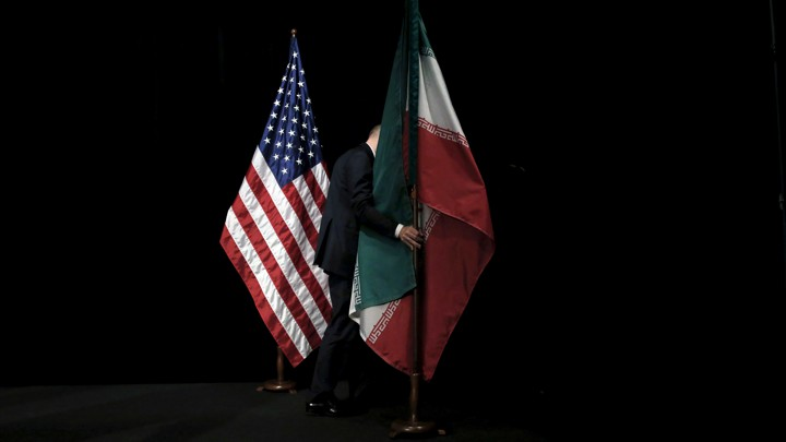 A man on a black stage removing the Iranian flag