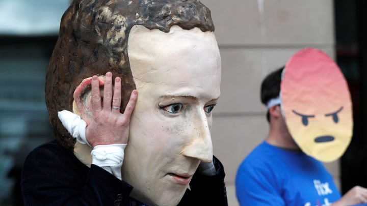 A demonstrator wears a giant mask of Facebook CEO Mark Zuckerberg.