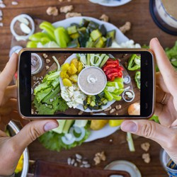 A person uses a smartphone to photograph a platter of vegetables and vegan mayonnaise.