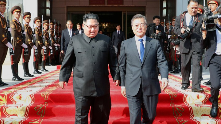 Kim Jong Un and Moon Jae In walking down carpeted steps
