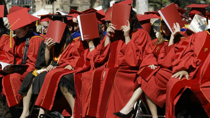 Women in graduation gowns covering their faces