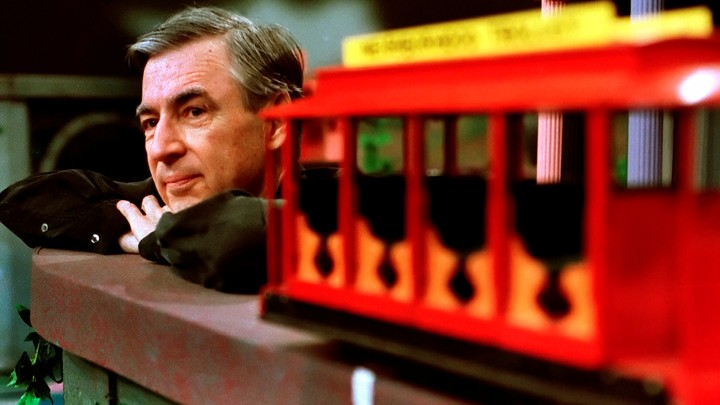 Fred Rogers resting near a trolley on a TV set
