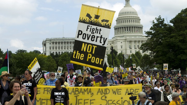Picture of a protest, with signs that say Fight Poverty NOT the Poor.