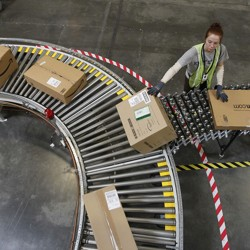 A worker loads Amazon packages onto a conveyor belt.