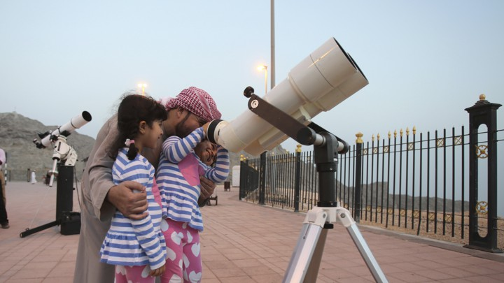 A father holds his two daughters while they look through a telescope.