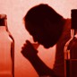A silhouette of a man drinking from a cup next to bottles of wine and liquor