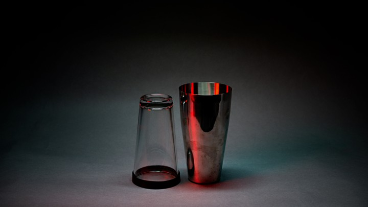 A photo illustration of a beer glass and cocktail mixer