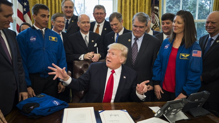 President Trump sits at the Resolute Desk surrounded by men in suits and two people in NASA jackets.
