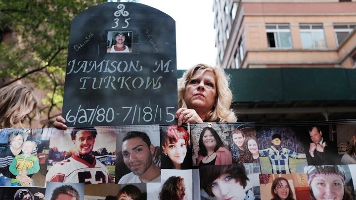 A woman holds a sign made to look like a gravestone next to photographs of young people.