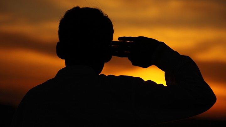A boy salutes at sunset