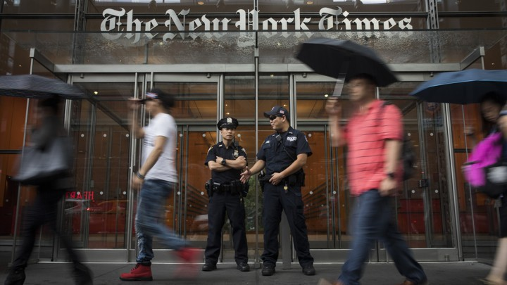 Members of the New York City Police Department stand outside the headquarters of The New York Times.