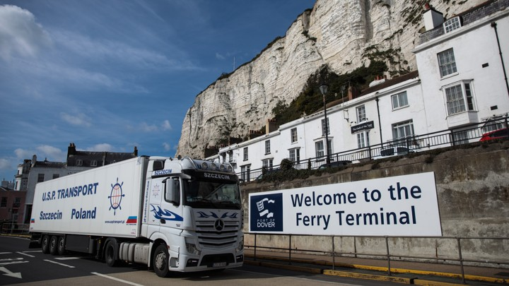 "A truck passes a cliff and a sign that says ""Welcome to the Ferry Terminal."""