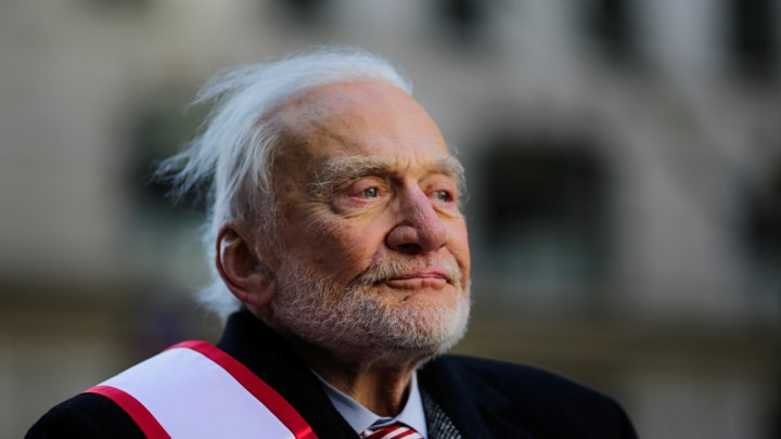 An elderly man with white, wispy hair looking off into the distance