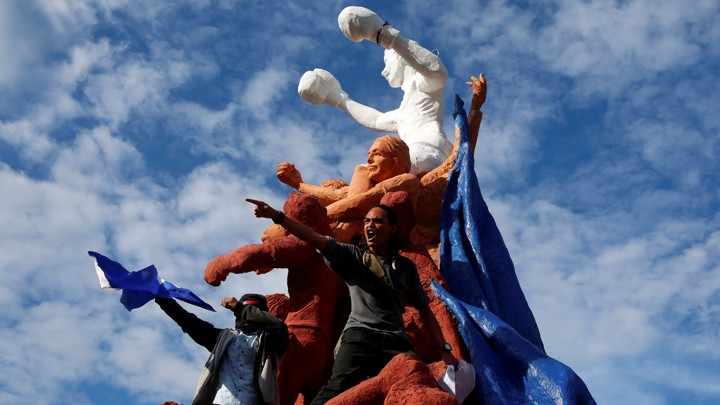 Protestors hold Nicaraguan flags standing on a statue