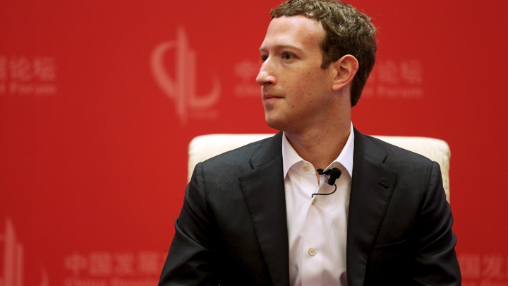 Mark Zuckerberg sits on a chair against a red background.