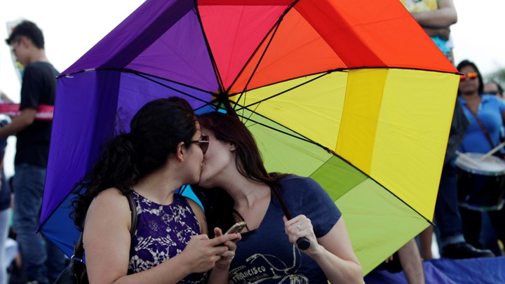 Two women kiss under a rainbow umbrella.