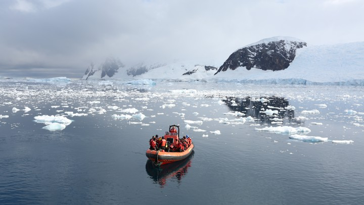 A small boat floats in Antarctica