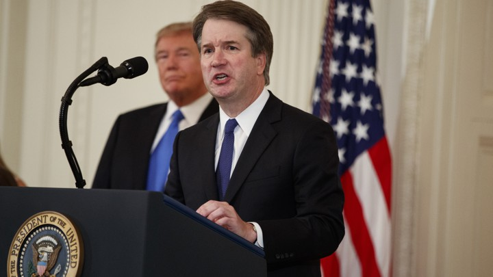 Brett Kavanaugh speaks at a podium with President Trump and an American flag in the background