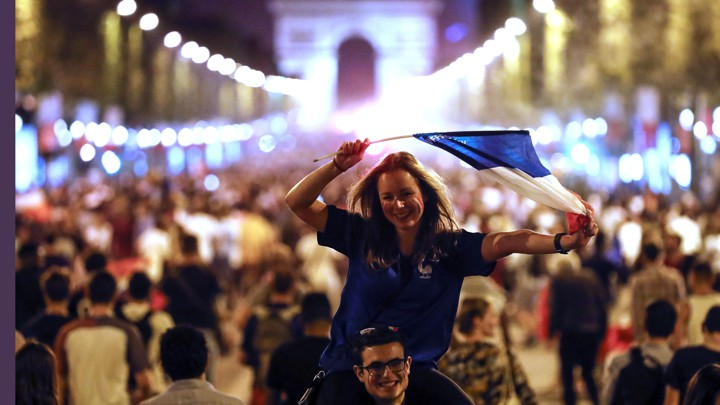 People celebrate on the Champs-Élysées, with the Arc de Triomphe in the background, after the semifinal match between France and Belgium at the 2018 World Cup