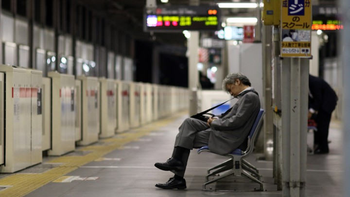 A man in business attire sleeps on a subway bench