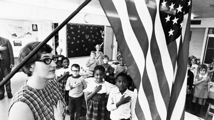 A teacher and her schoolchildren pledging allegiance to the American flag