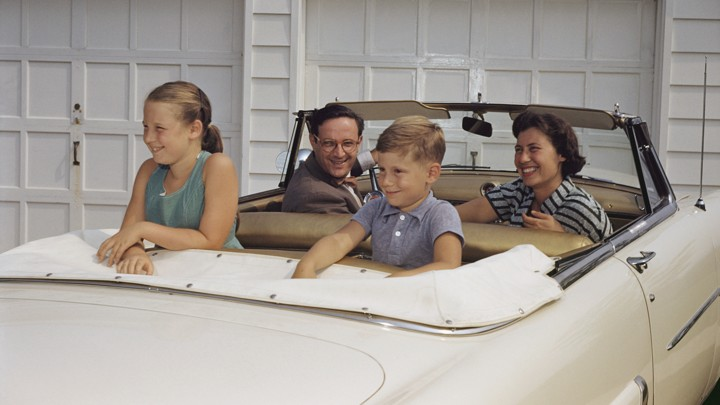 A family sits in a white convertible
