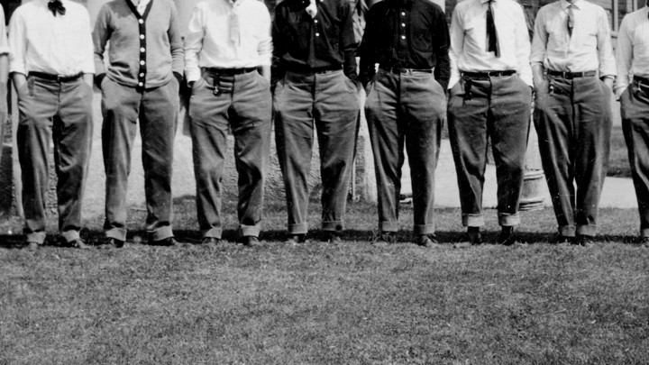 Fraternity men stand with their hands in their pockets, with their heads out of frame.