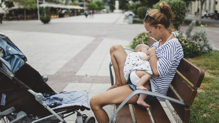 A baby is breastfed by a woman